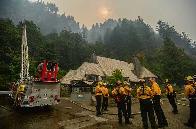 OUTLOOK FILE PHOTO - Firefighters take a break from defending Multnomah Falls Lodge last fall during the Eagle Creek Fire that swept through the Columbia River Gorge.