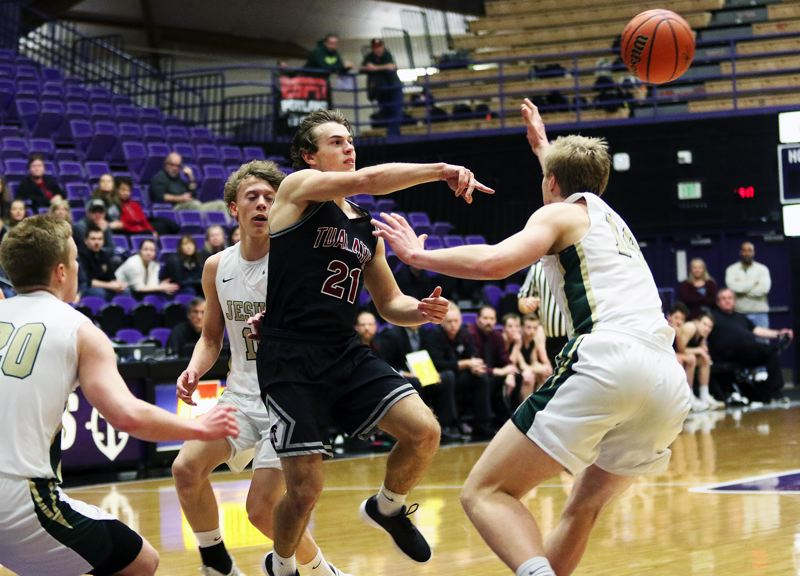 DAN BROOD - Tualatin senior Lucas Noland rifles a pass past Jesuit's Sam Handley during Friday's consolation bracket semifinal game at the Class 6A state tournament. The Wolves got a 53-49 win.