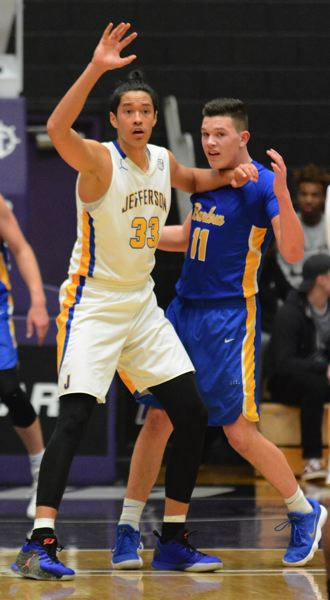OUTLOOK PHOTO: DAVID BALL - Barlow's Dominic Jacoby works to defend Jefferson's 6 foot, 10 inch center Kamaka Hepa, who has committed to the University of Texas.