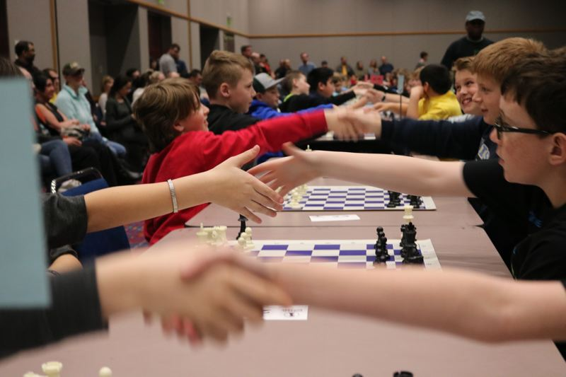 TRIBUNE PHOTO: ZANE SPARLING - Elementary aged students shake hands before begining to play chess during the 51st annual Chess for Success tournament in Portland on Saturday, March 10.