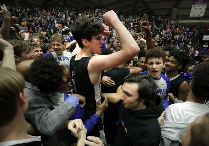 TRIBUNE PHOTO: JONATHAN HOUSE - Grant senior post Kelton Samore and teammates are surrounded by cheering fellow students and fans after their team won the Class 6A boys basketball championship Saturday night at Chiles Center.