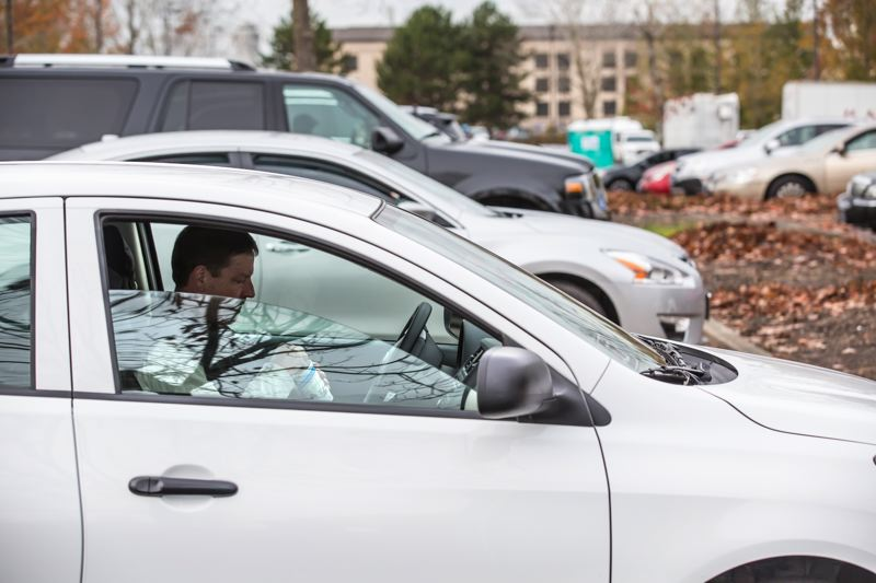 TRIBUNE PHOTO: JONATHAN HOUSE - An Uber/Lyft driver has a snack while waiting for a fare at the Transportatiion Network Company hold lot near the Portland Airport.