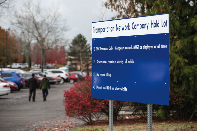 TRIBUNE PHOTO: JONATHAN HOUSE - A sign points out the rules at the Transportatiion Network Company hold lot near Portland Airport.