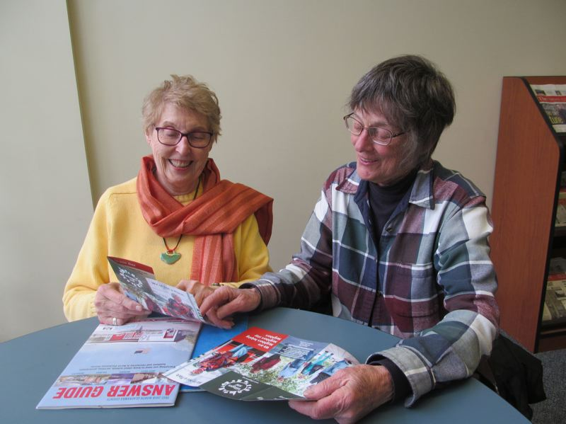 PHOTO BY ELLEN SPITALERI - Kay Weaver, left, and Pat Carter, both residents of unincorporated Clackamas County, look over brochures from Villages NW. They hope to bring a village to the Milwaukie area.
