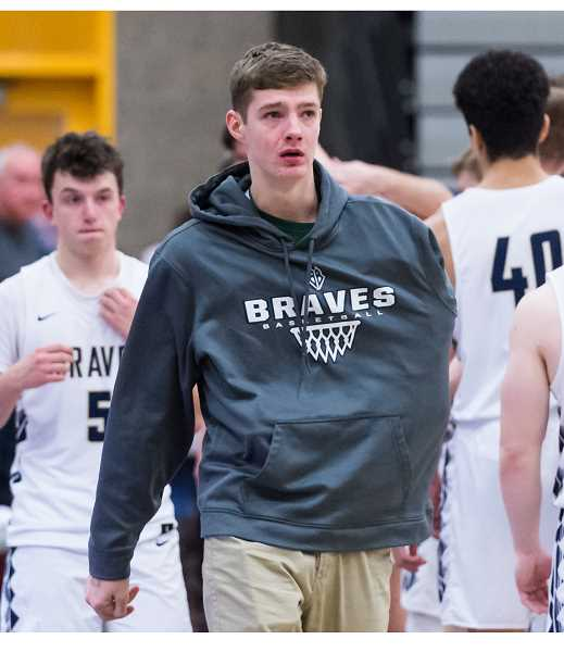 STAFF PHOTO: CHRISTOPHER OERTELL - A disappointed Dalton Renne walks off the court with his teammates following the Braves' state tournament third place game loss to Newport. Renne was injured early in Banks' semifinal game and the team never recovered.