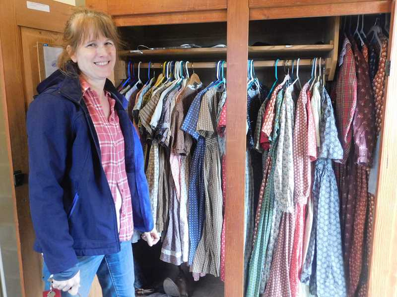 ESTACADA NEWS PHOTO: EMILY LINDSTRAND - Chris Bento is the head costume designer at Philip Foster Farm. Here, she stands in front of the historical sites closet of costumes for volunteers.
