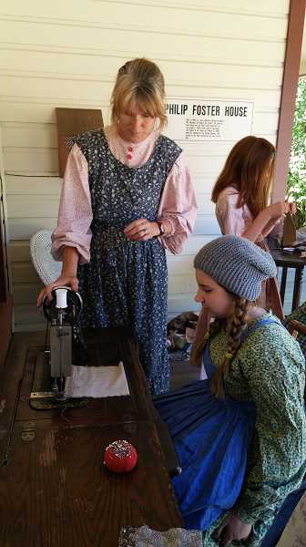 CONTRIBUTED PHOTO: PHILIP FOSTER FARM - Chris Bento works with students at Philip Foster Farm's summer camp on the sewing machine.