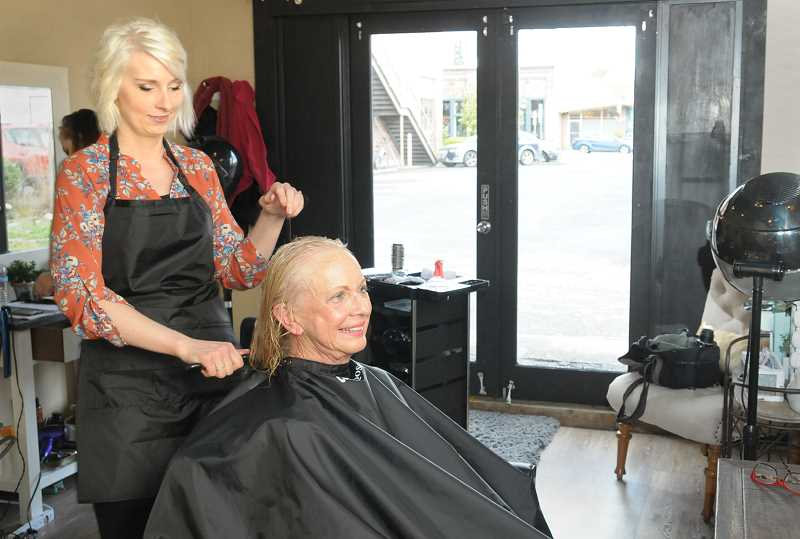 GARY ALLEN - Salon Debut co-owner Laura Olson tends to customer Linda Ault's hair during an appointment last week.