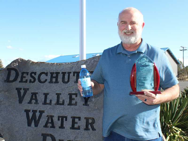 HOLLY M. GILL - Deschutes Valley Water District General Manager Ed Pugh displays the district's award for best overall water in the state. Pugh holds a bottle of the district's pure water, which comes from Opal Springs.