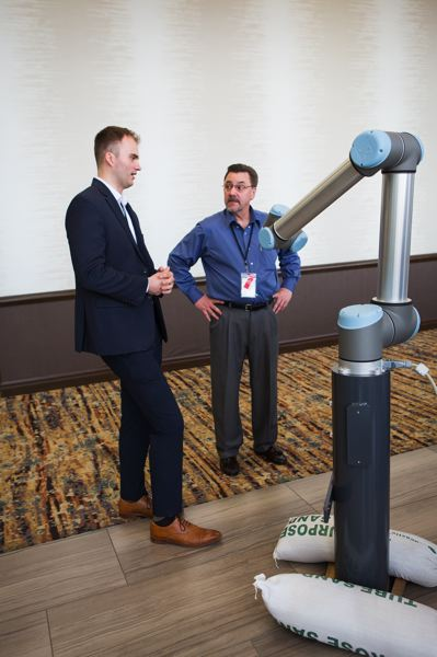 PAMPLINMEDIA GROUP: ADAM WICKHAM  - Ben Courtright, an Oregon-based employee of Universal Robots, shows off a colab robot at the Oregon Manufacturers Summit. Colabs are designed to be easily programmable for simple repetitive tasks, and to work safely alongside humans.