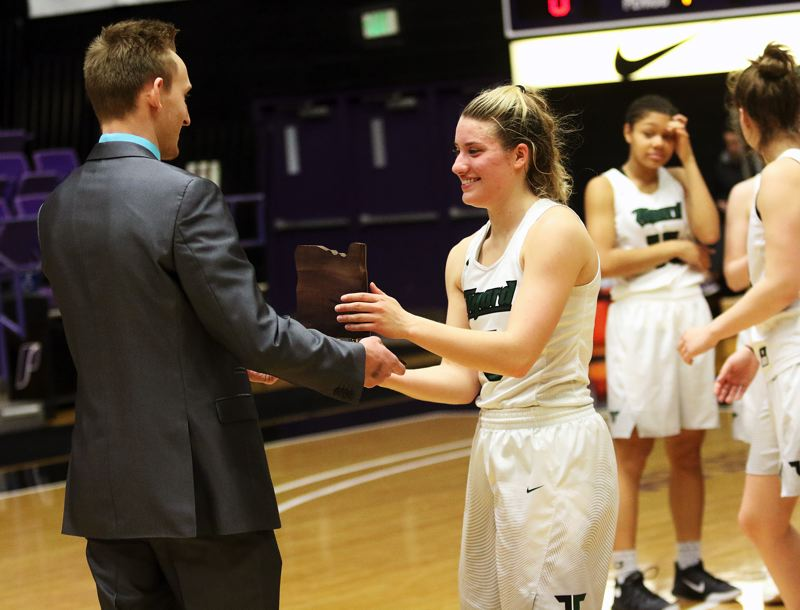 DAN BROOD - Tigard High School senior Gabby McGaughey is presented the fourth-place trophy Saturday at the Class 6A basketball state tournament.