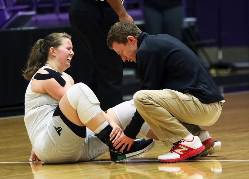 DAN BROOD - Tigard junior post Dani Lyons has her ankle checked by Tigard High School athletic trainer Travis Johannes during Saturday's state tournament game.
