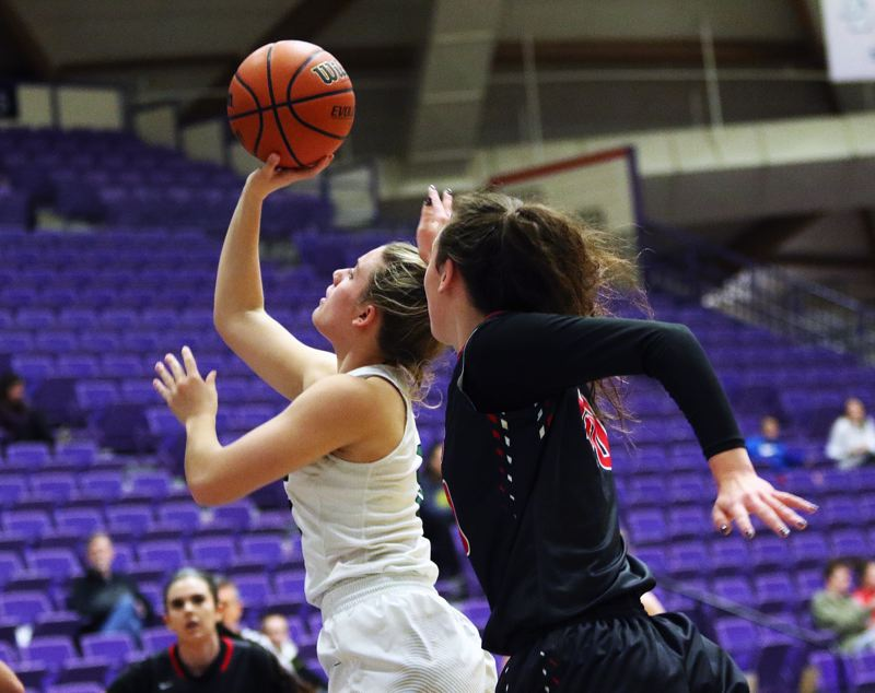DAN BROOD - Tigard senior Gabby McGaughey (left) looks to put up a shot as she drives to the basket during the Tigers' state tournament win over Clackamas.
