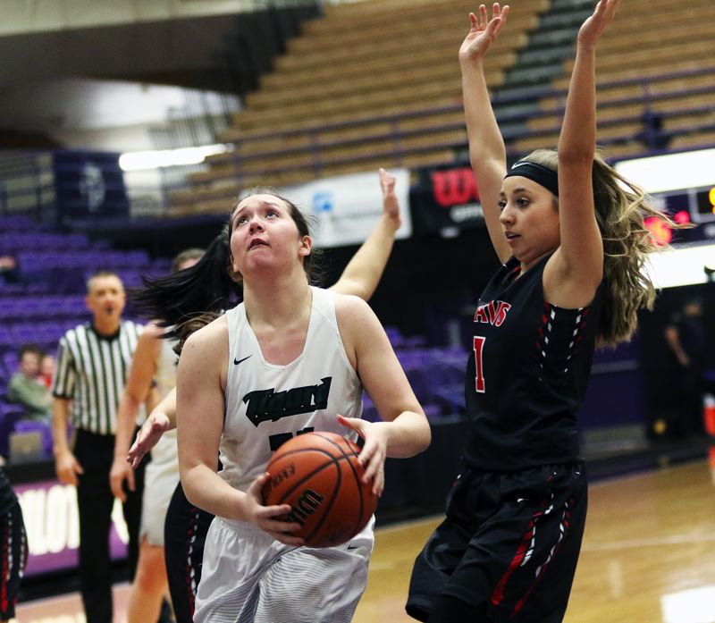 DAN BROOD - Tigard junior guard Paige LaFountain (left) looks to get past Clackamas junior Payton Mongelli and go up to the basket during the Tigers' state tournament victory on Saturday.