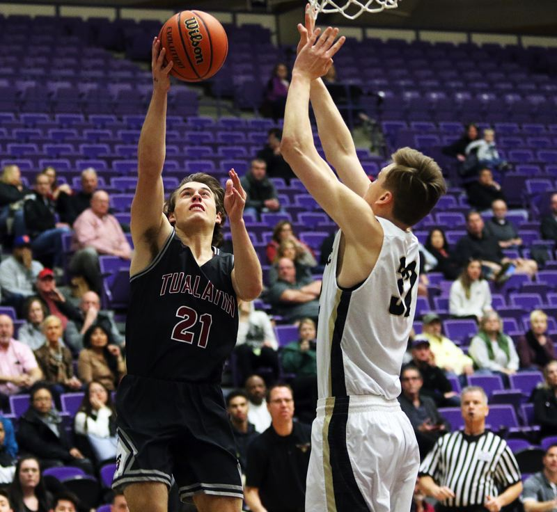 DAN BROOD - Tualatin senior Lucas Noland (left) tries to get a shot over 6-foot-10 Southridge senior Filip Fullerton.
