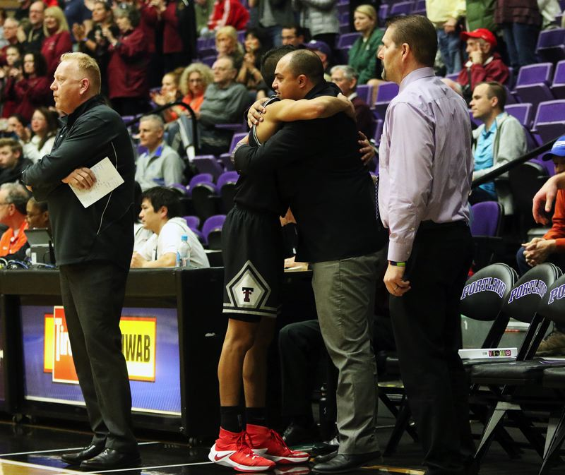 DAN BROOD - Tualatin senior Alexis Angeles gets a hug from Timberwolf assistant coach Bubba Lemon as he leaves the court late during Saturday's Class 6A state tournament game.