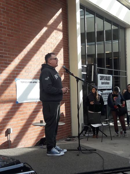 STAFF PHOTO: MARK MILLER - The Rev. Chuck Currie, Pacific University's chaplain, urges students to organize for political action Wednesday at the Washburne University Center.