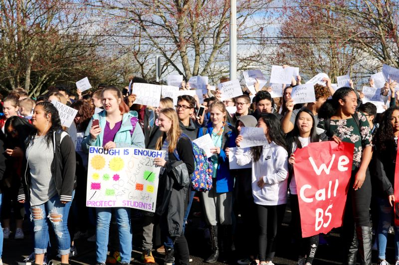 OUTLOOK PHOTO: ZANE SPARLING - Centennial High School pupils hold up signs bearing the names of students slain in Florida during a 17-minute walk out on Wednesday, March 14.