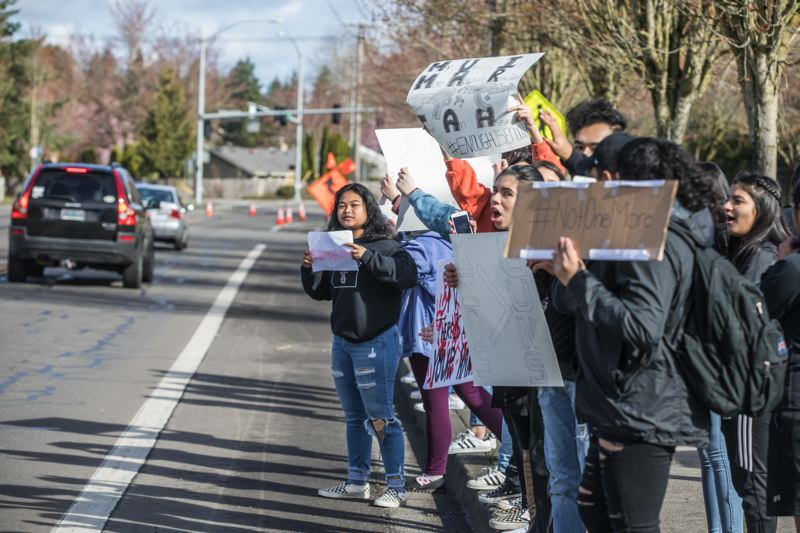 PAMPLIN MEDIA GROUP: JONATHAN HOUSE - Students outside of Tualatin High School wave signs at passing motorists during the #Enough walkout. They were part of a student-organized protest of gun violence and school shootings.