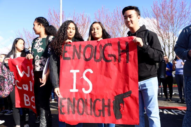 OUTLOOK PHOTO: ZANE SPARLING - Students display a banner reading 'Enough Is Enough' at Centennial High School on March 14.