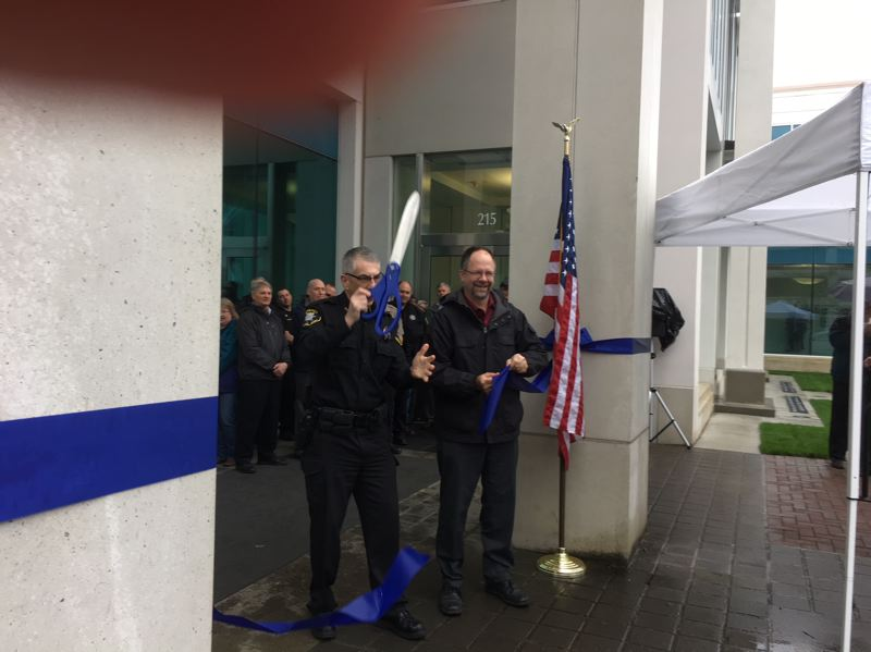 PAMPLIN MEDIA GROUP: PETER WONG - Sheriff Pat Garrett wields the scissors while Board Chairman Andy Duyck holds the blue ribbon at a ceremony Tuesday, March 13, to observe completion of seismic upgrades at the Washington County Law Enforcement Center in Hillsboro.