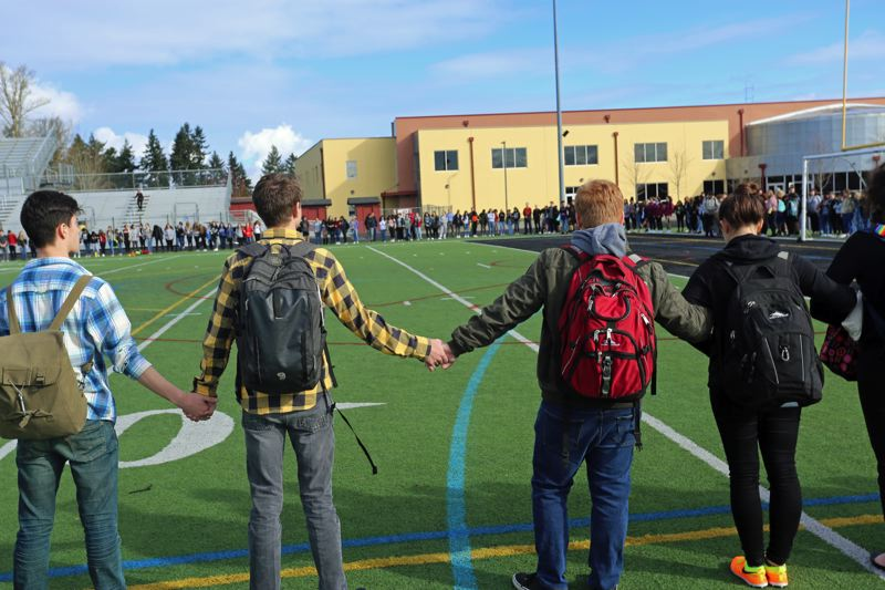 PHOTO COURTESY OF ERIC BALLAS - Students at Southridge High School link hands around the football field in a show of solidarity.