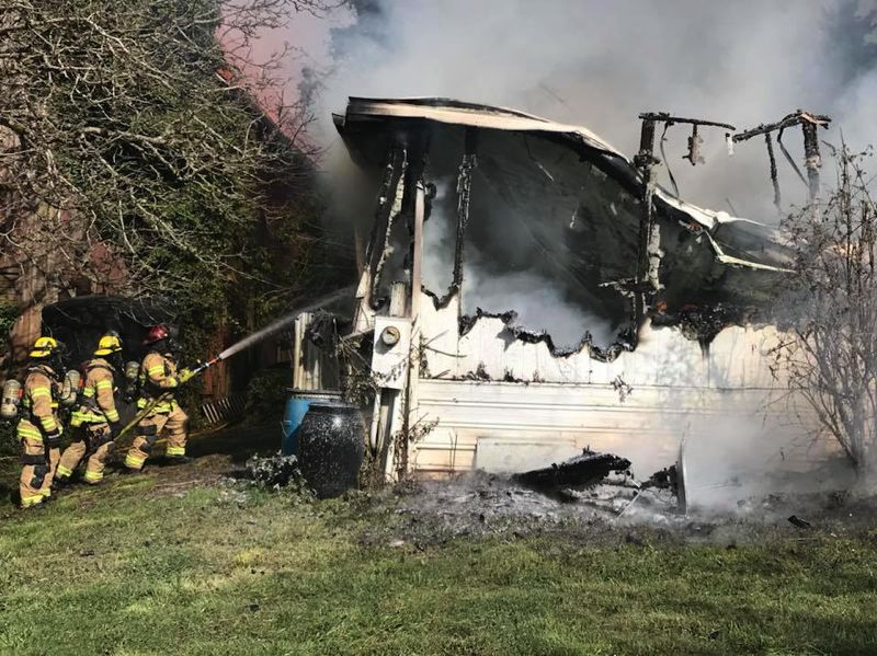 COURTESY PHOTO: CORNELIUS FIRE DEPARTMENT - Firefighters use a fire hose to put out hot spots in the remnants of a trailer home off Gnos Road.