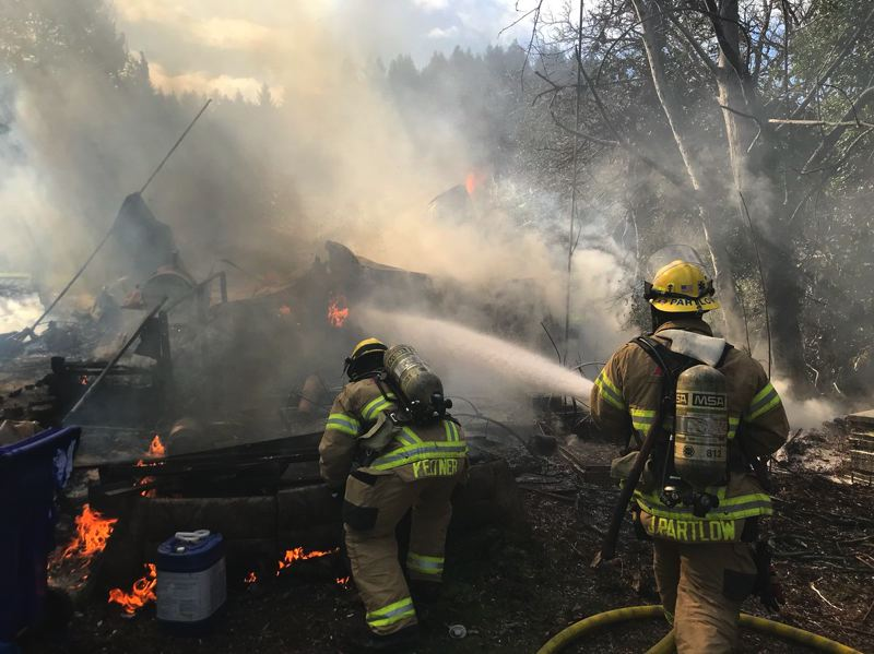 COURTESY PHOTO: CORNELIUS FIRE DEPARTMENT - Firefighters spray down smoldering flames in the ruins of a mobile home south of Cornelius on Wednesday.