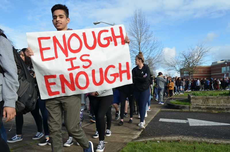 Students hold up signs as they march from Century High School on Wednesday, March 14
