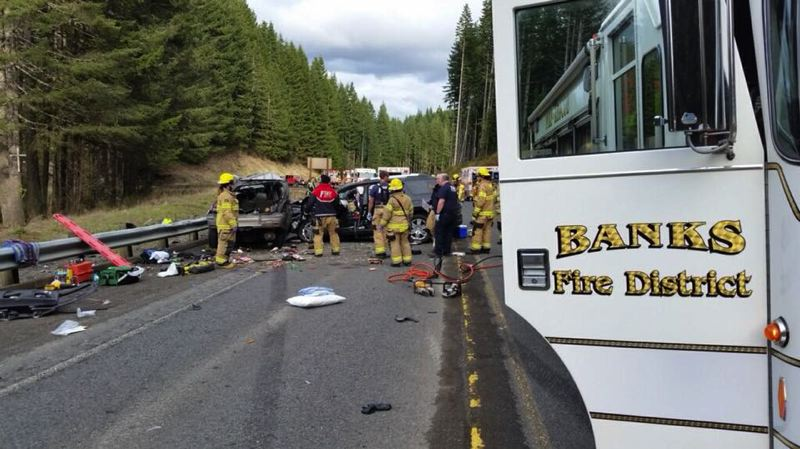 COURTESY PHOTO: BANKS FIRE DISTRICT - First responders attend to the scene of a crash Friday on Highway 26 that reportedly involved four vehicles, left two dead and injured five more.