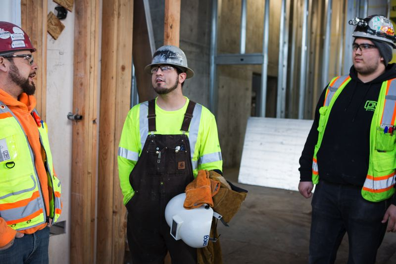 PAMPLIN MEDIA GROUP: ADAM WICKHAM - 19 year old sheet metal apprentice Cristian Torres (right) on the job site with his foreman Junior Fidencio (left).  Torres heard about the five year apprenticeship from Fidencio, a family friend, and jumped right in at $19.80 an hour rising to $24 an hour next year. Pipefitter Antonio Ruiz, 26,  (center) is relatively new to construction too.