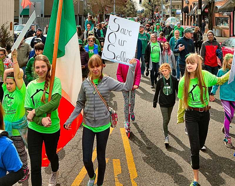 DAVID F. ASHTON - Taking it to the streets: Marching in the St. Agatha St. Patricks Day Parade, Sellwood and Woodstock Community Center supporters had their placards in hand.