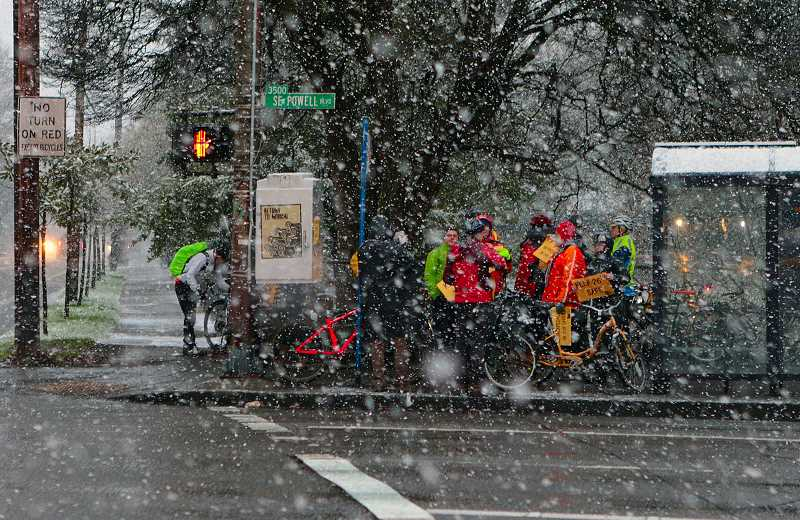 DAVID F. ASHTON - Folks protesting against removing bike lanes on S.E. 26th Avenue were hard to see in the heavy snowfall, as they stood near Cleveland High on Powell Boulevard.