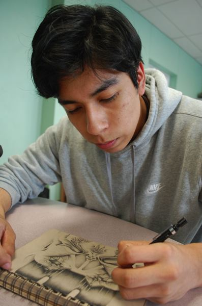 PHOTO BY RAYMOND RENDLEMAN - Milwaukie senior Angel Reyes is working on various pencil-on-paper drawings for the Advanced Placement exam.