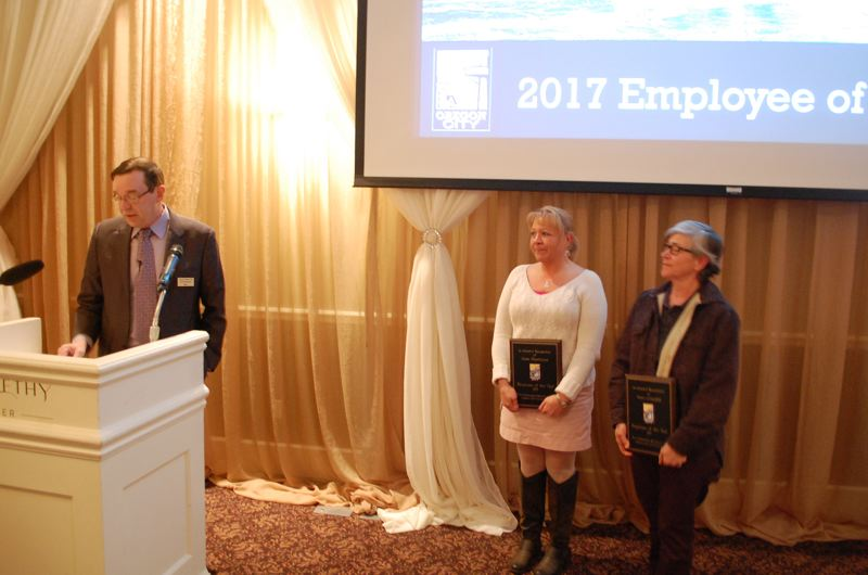 PHOTO BY RAYMOND RENDLEMAN - Alisa Heathman and Anne Crandall received dual employees-of-the-year honors from Oregon City Mayor Dan Holladay at the March 15 event.
