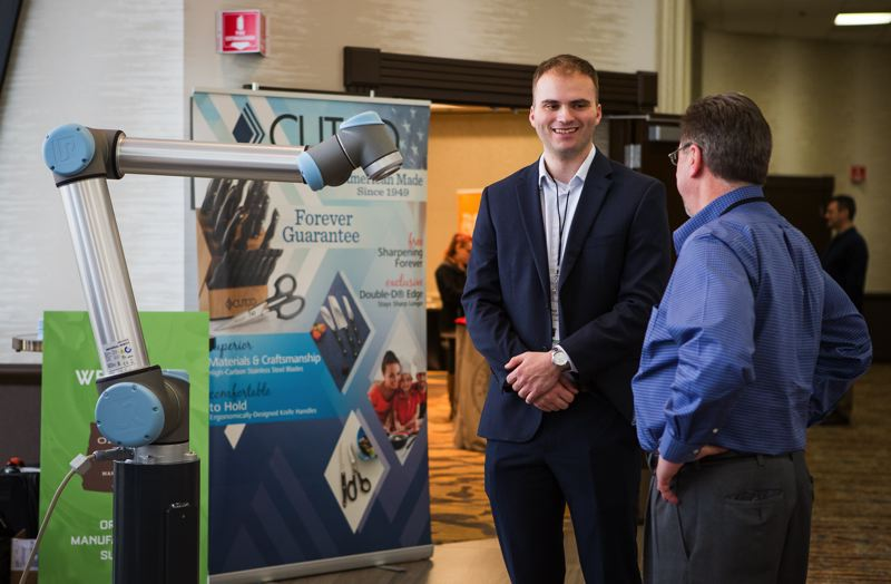 PHOTO BY ADAM WICKHAM  - Ben Courtright, an Oregon-based employee of Universal Robots, shows off a colab robot at the Oregon Manufacturers' Summit. Colabs are designed to be easily programmable for simple repetitive tasks, and to work safely alongside humans.