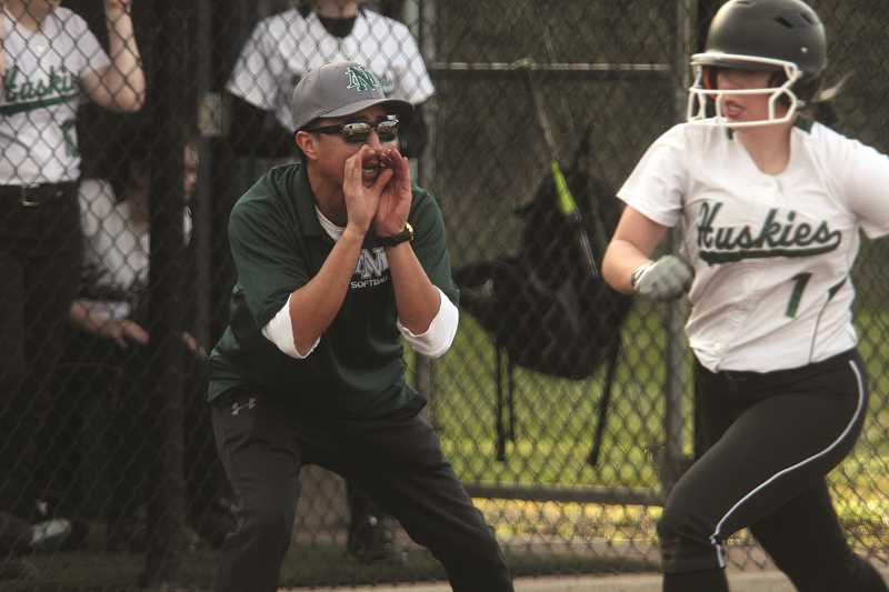PHIL HAWKINS - North Marion head softball coach Jonathan Santos urges junior Samantha Baylie to round third base and score in the Huskies' 20-6 loss to Central in the team's home opener on March 14. Baylie played for Santos' 18U traveling team, the Canby Rebels, in the offseason.