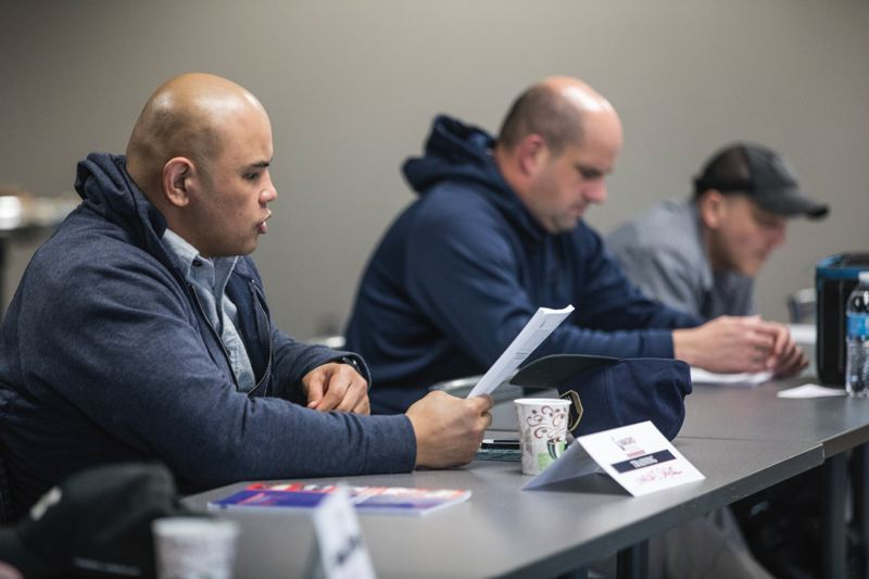 PORTLAND TRIBUNE: JONATHAN HOUSE - Officer Charles Saguil reads from the training manual at the School Resource Officers training session hosted by the Portland Police Bureau.