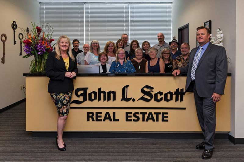 PHOTO COURTESY: ANNIE GUSTAFSON - Ronda Camman and Craig Fahner pictured with the team at John L. Scott's Portland-metro office in Gresham.