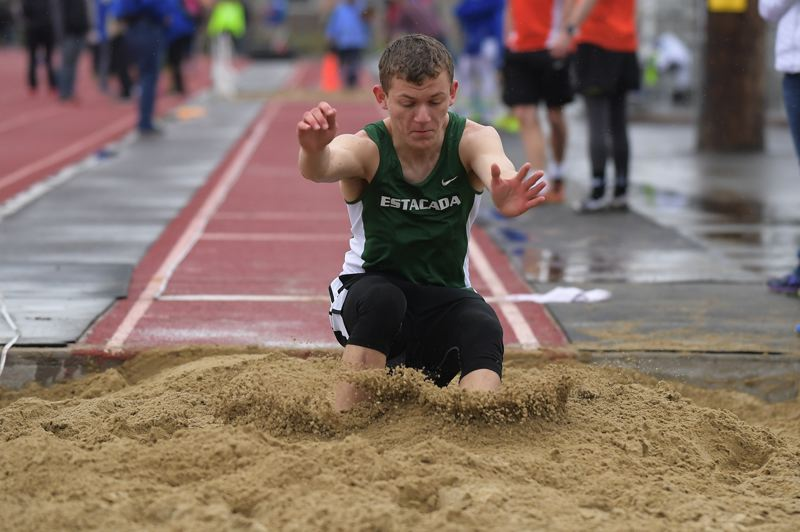 PAMPLIN MEDIA GROUP - Estacada's Logan Stamm lands in the long jump pit.