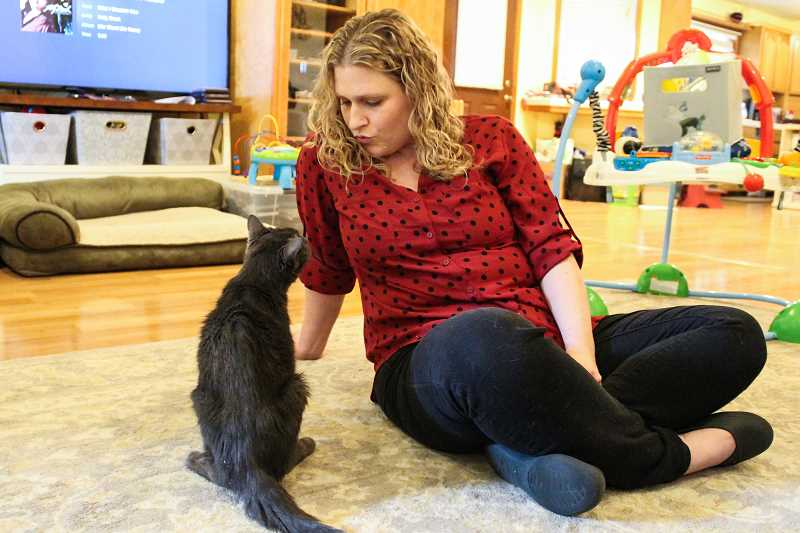STAFF PHOTO: GEOFF PURSINGER - Amber Neufeld, of Midway, talks to her 16-year-old cat, Buddy. The two have been inseparable since college, but Neufeld recently put the cat on hospice home care to make him more comfortable in his old age.
