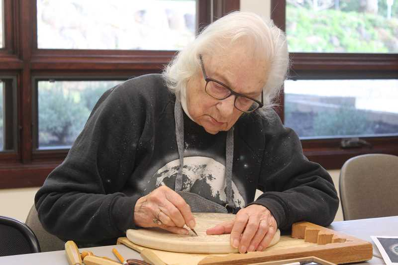 TIDINGS PHOTOS: PATRICK MALEE - Beverly Lynds concentrates on her carving of a 15th century piece by the Italian sculptor Luca della Robbia.