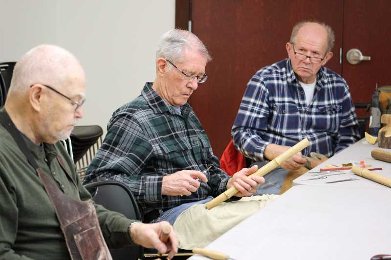 From left, John Bezayiff, Ron Williamson and Jay Rice chat while they carve.
