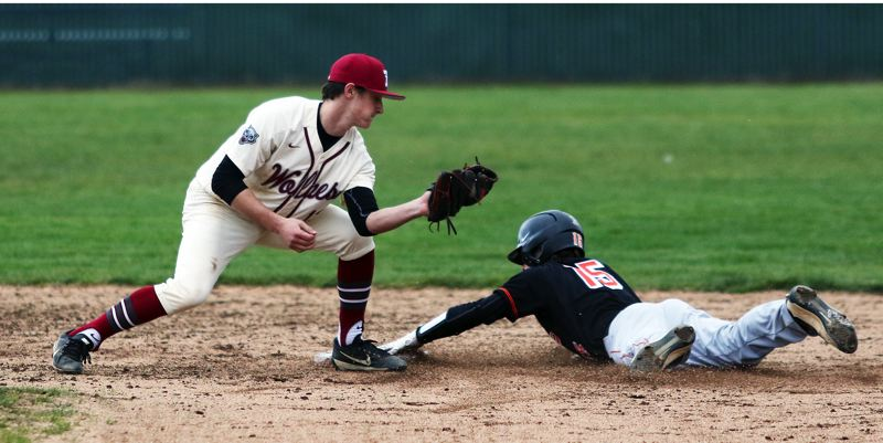 TIMES PHOTO: DAN BROOD - Tualatin senior Colby Jackson (left) looks to put a tag on sliding Beaverton junior Connor Patrick during last weeks non-league game.