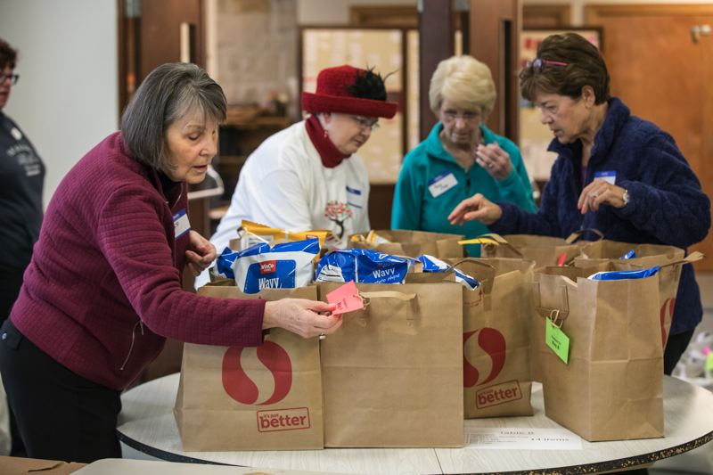 TIMES PHOTO: JONATHAN HOUSE - Buff Holtman checks tags on outgoing grocery bags that will be delivered to homeless students at Beaverton High School over Spring Break.