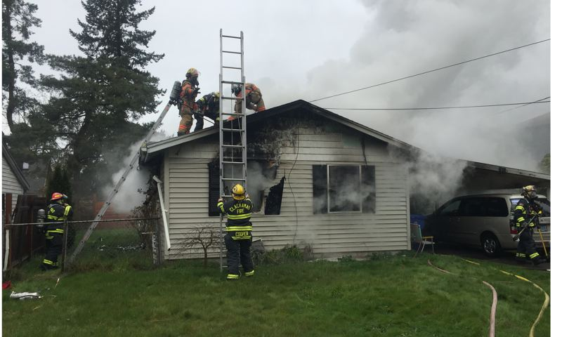 PHOTO COURTESY: CLACKAMAS FIRE - Clackamas firefighters work to control a fire that broke out Thursday at a house on Overland Street in Milwaukie.