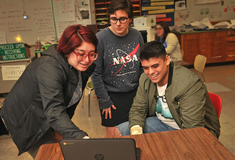 OUTLOOK PHOTO: VERN UYETAKE - Bobby Asa returned to Barlow High School this semester after his accident and is checking out the news in his journalism class with Vic Sanchez, senior, left, and MacKenzie Cochran, junior.