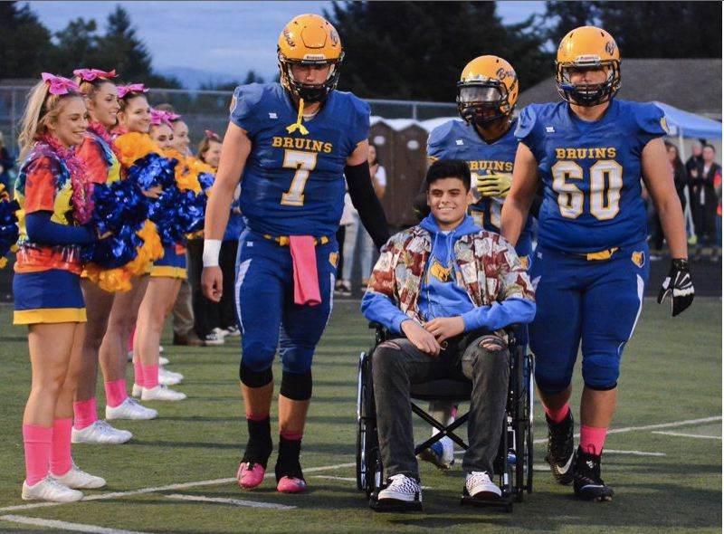 OUTLOOK PHOTO: DAVID BALL  - Bobby Asa, who played football for Barlow, was all smiles while being escorted onto the field by teammates Austin Davis (7), Jobi Malary (background) and Triston Stauffer (60) for a celebration in October.