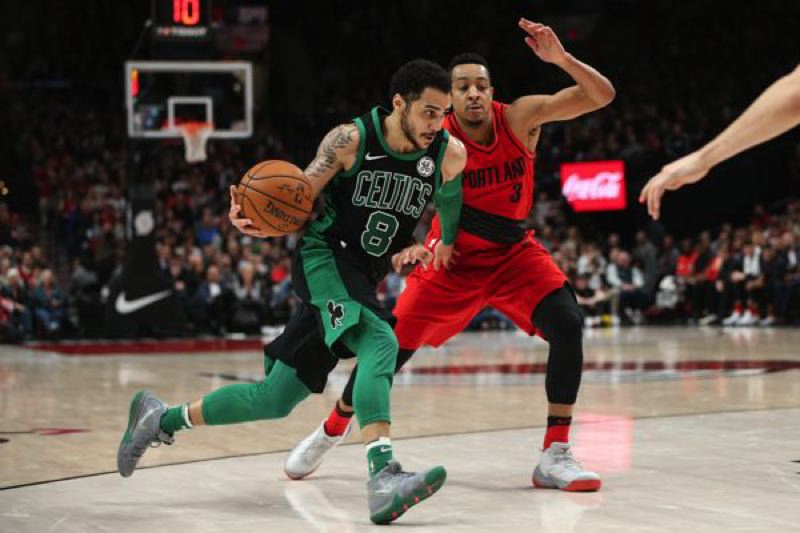 Shane Larkin (left) of the Boston Celtics drives to the basket against CJ  McCollum of the Trail Blazers.