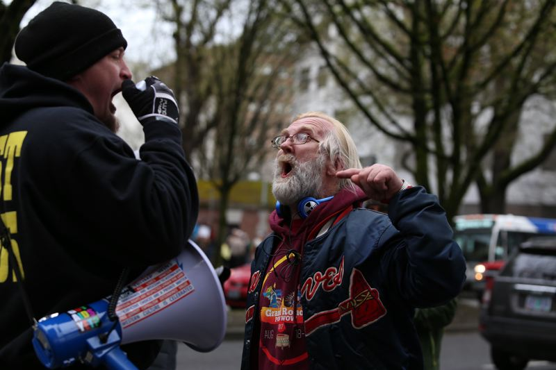 TRIBUNE PHOTO: JESSIE DARLAND  - A counter protester speaks into a bullhorn while being confronted by an activist at the 'March for Our Lives' in downtown Portland on Saturday, March 24.